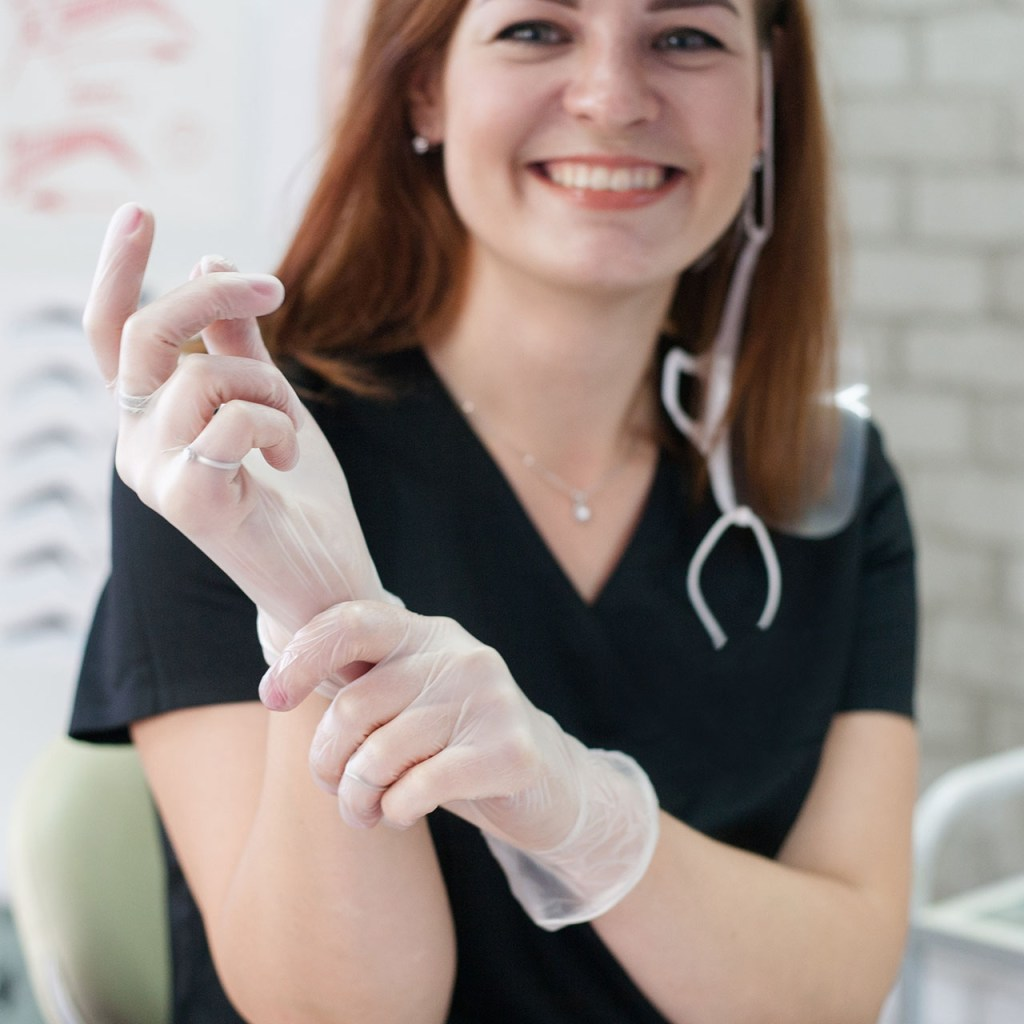 Successful career in medicine. Portrait of female health and beauty care worker. Confident cheerful woman wearing gloves, smiling.