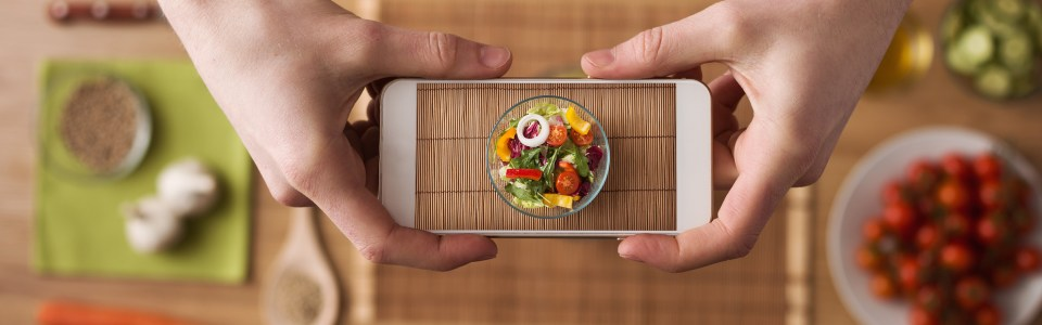 Man holds a smartphone over food