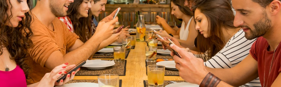 Group of friends at a restaurant on their cellphones