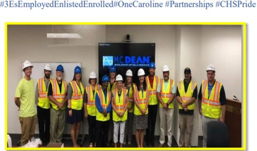 Senior Staff posing in hard hats and safety vests at MC Dean