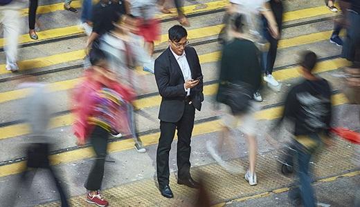 Businessman using smart phone amidst crowd