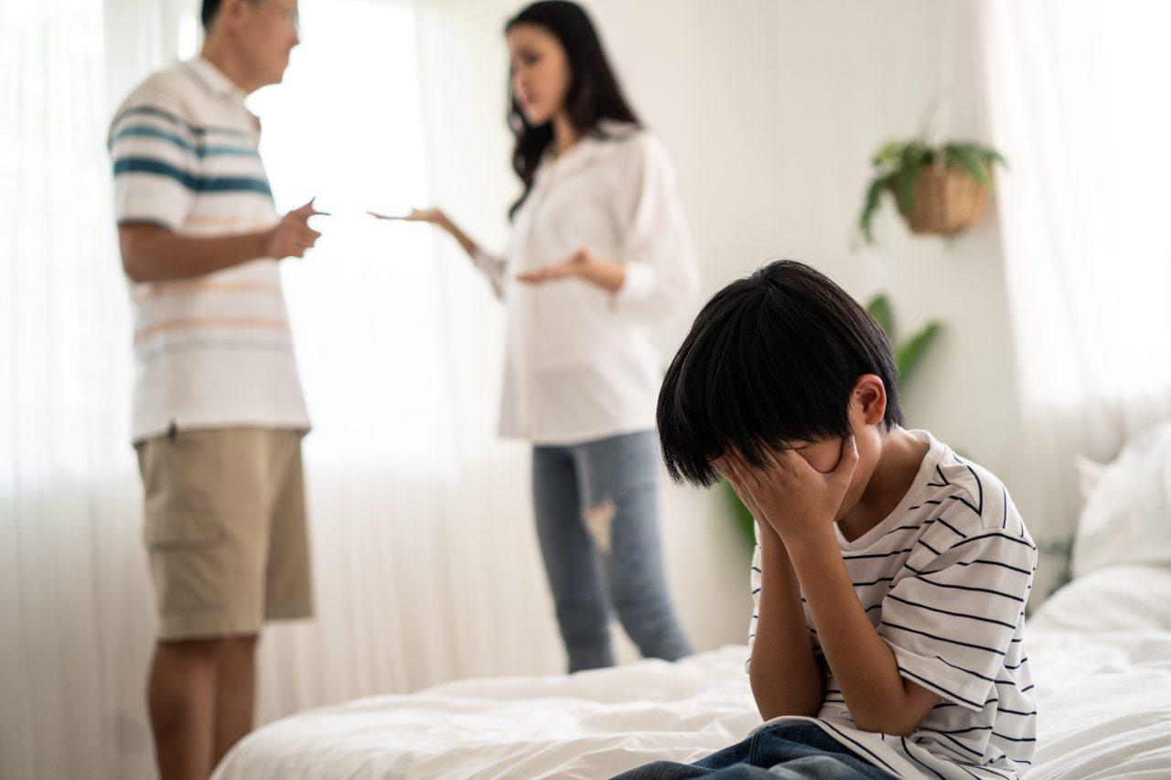 Forældremyndighed og konflikt om omskæring. Ulykkeligt barn og forældre, der skændes i baggrunden.
