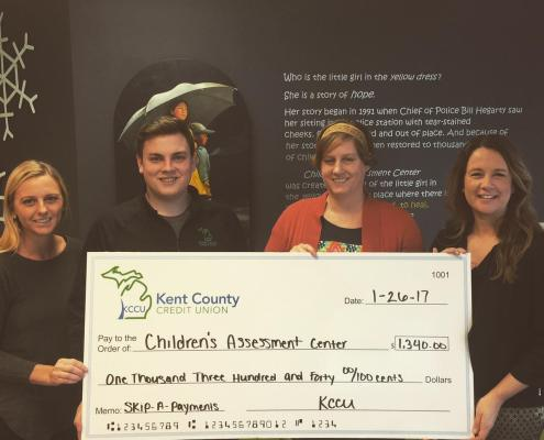 KCCU giving donation to Children's Assessment Center