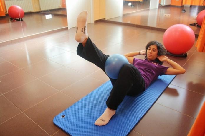 Ejercicio de Pilates con pelota entre las piernas