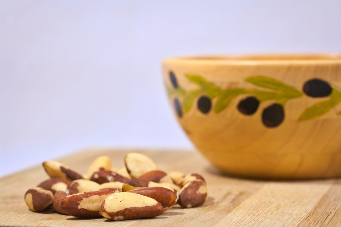 Brazil nuts next to a bowl. Brazil nuts are a rich source of zinc. Why zinc lozenges when you can acquire zinc from whole food sources?