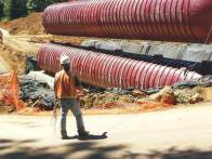 A worker supervises the installation of a 40,000 gallon wastewater tank