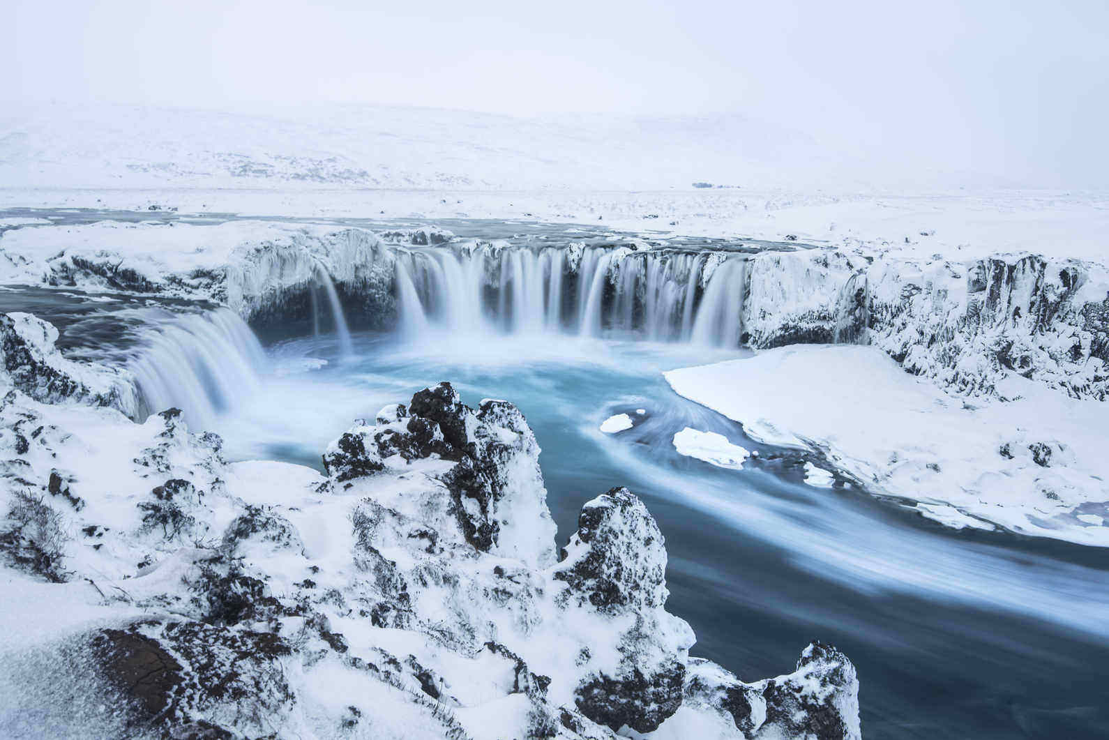 Godafoss waterfall in Iceland covered in snow, with a white landscape