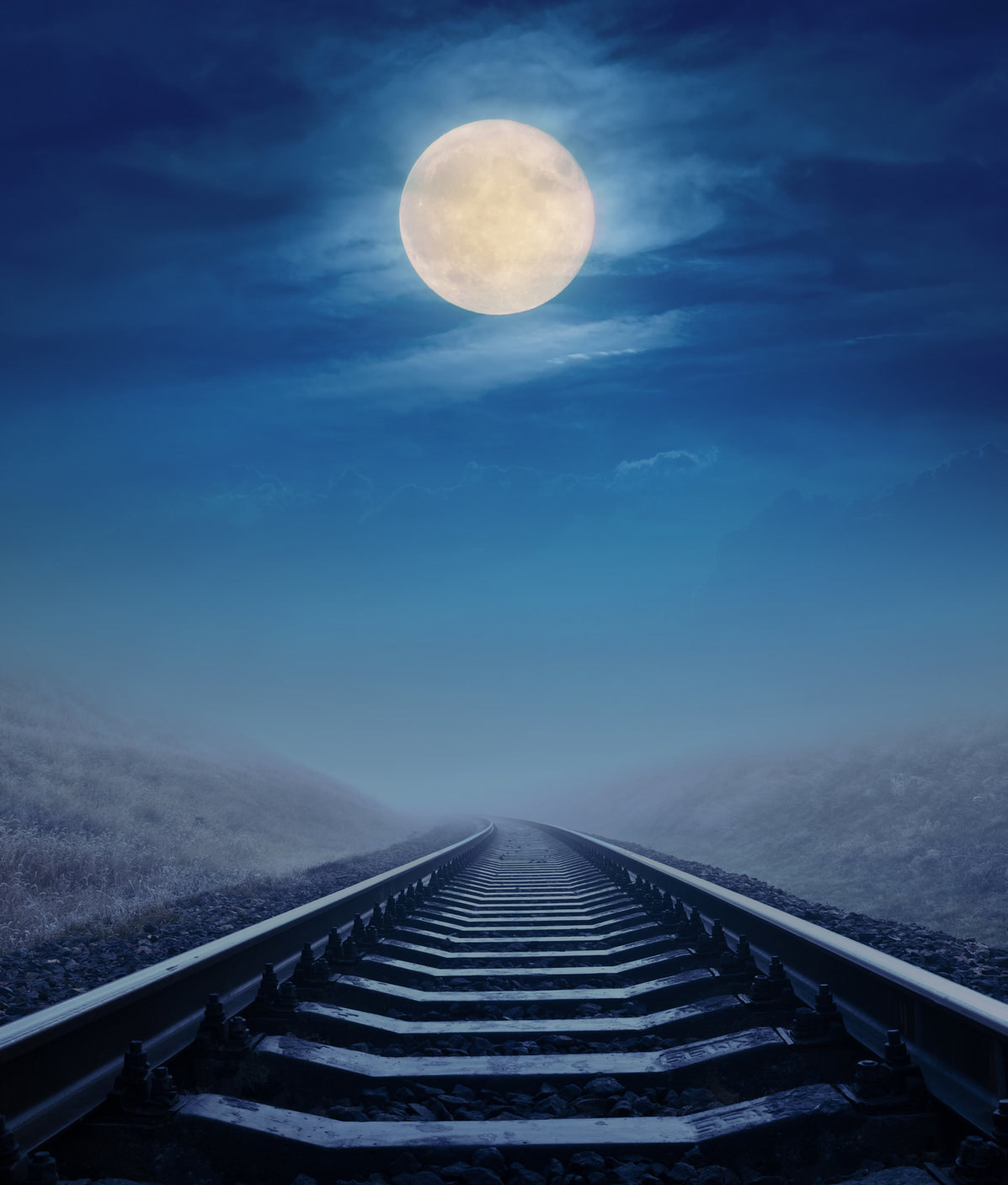 Full moon in clouds over railroad