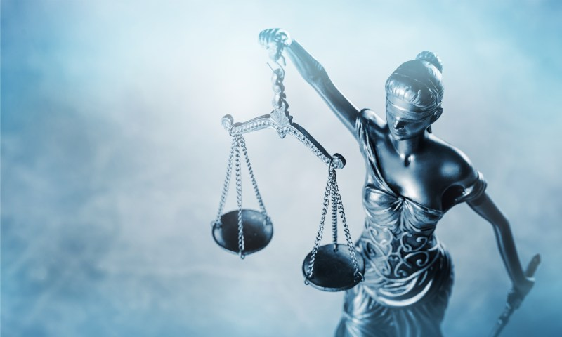 A blind-folded lady justice holding a set of scales.