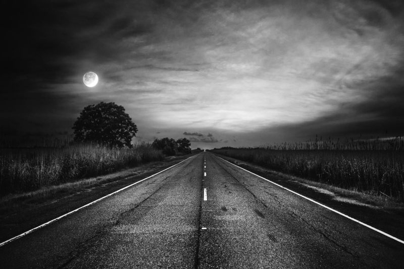 A black and white tarred road heading into the distance with the moon in the left had corner.
