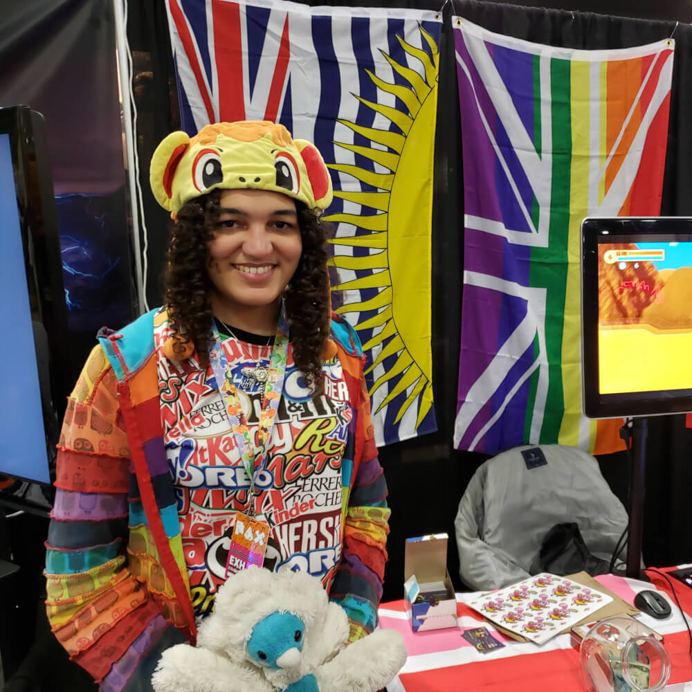 Rina Purdy stands near a colorful booth with a brightly-colored hat and rainbow-colored shirt.