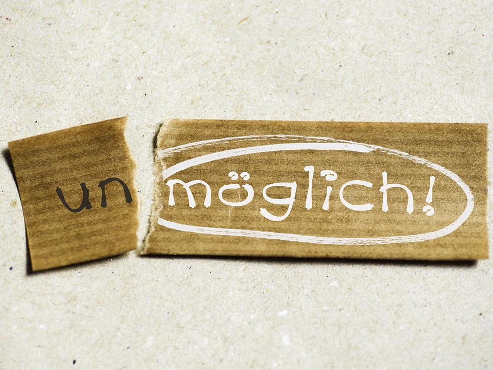 """Ein durchgebrochenes Holzbrett, auf einem Teil steht """"un"""" auf dem anderen """"möglich"""""""