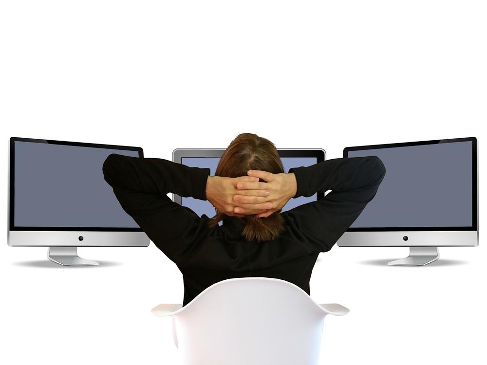 Eine Person lehnt sich entspannt vor drei Monitoren zurück mit hinter dem Kopf gekreuzten Händen.