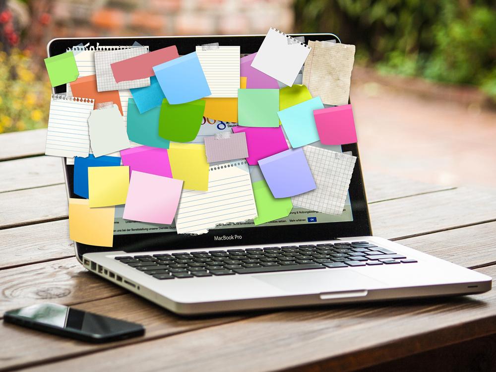 Laptopdisplay ist mit unterschiedlichsten bunten Post-its vollgeklebt, sodass man den Bildschirm kaum noch sehen kann.