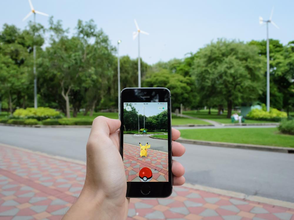 Ein Smartphone wird hochgehalten, darauf ist das Spiel Pokémon Go zu sehen.