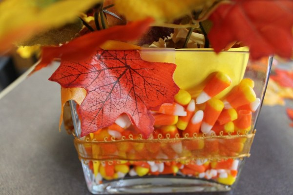 How To Make A Scarecrow Centerpiece. This fun centerpiece or tabletop Scarecrow is made completely with dollar store supplies. He's popping up from the leaves and keeping the candy corn safe. #diy #diyfall #falldecor #scarecrow #candycorn #dollarstore #dollarstoredecor Glue the loose leaves onto the edge of the vase with hot glue.