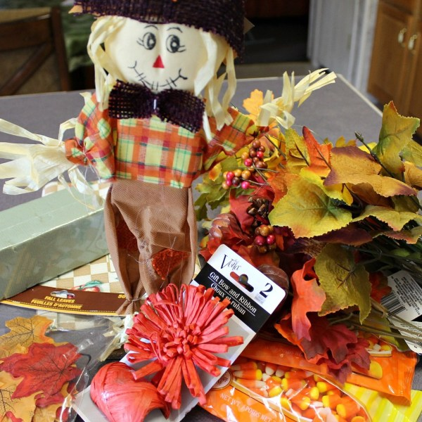 How To Make A Scarecrow Centerpiece. This fun centerpiece or tabletop Scarecrow is made completely with dollar store supplies. He's popping up from the leaves and keeping the candy corn safe. #diy #diyfall #falldecor #scarecrow #candycorn #dollarstore #dollarstoredecor
