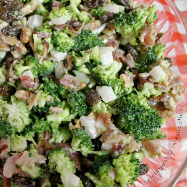 Broccoli Bacon Salad served in a glass bowl sitting on a table with a red and white checkered tablecloth