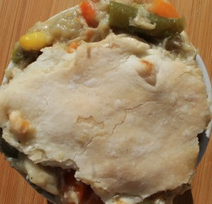 Chicken pot pie with vegetables spilling out of the top crust in a white bowl