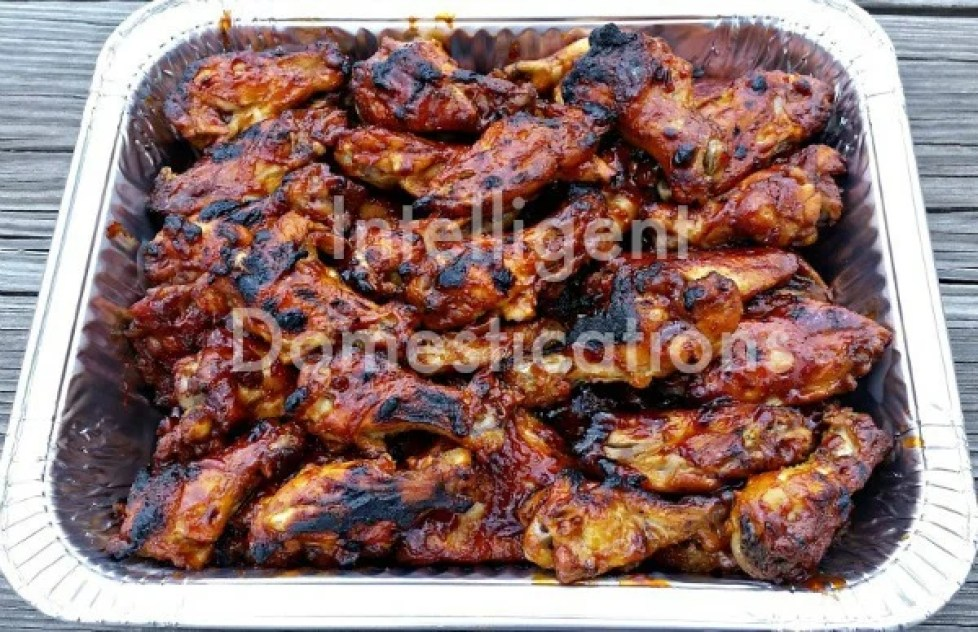 a foil pan filled with BBQ Chicken Wings