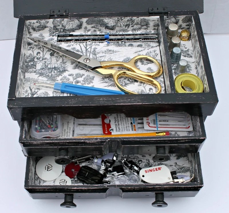 Sewing supplies inside a storage box with drawers