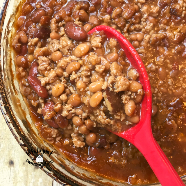 Baked beans in a big bowl with a red spoon lifting some up