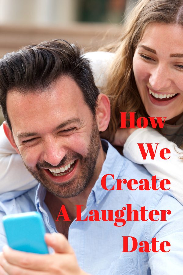 A couple sitting close laughing at something on a cell phone which he is holding in his hand