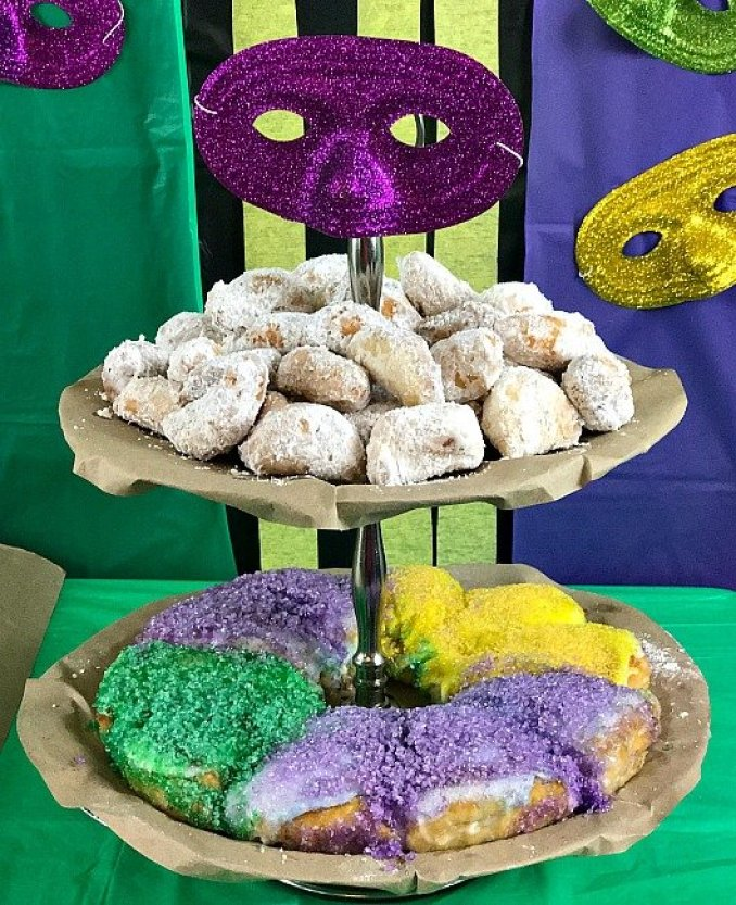A two tiered tray covered with brown paper holding Biscuit Biegnets and King Cake on a Mardi Gras party table