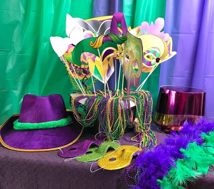 Mardi Gras dress up supplies on a table including masks, hats, beads and features