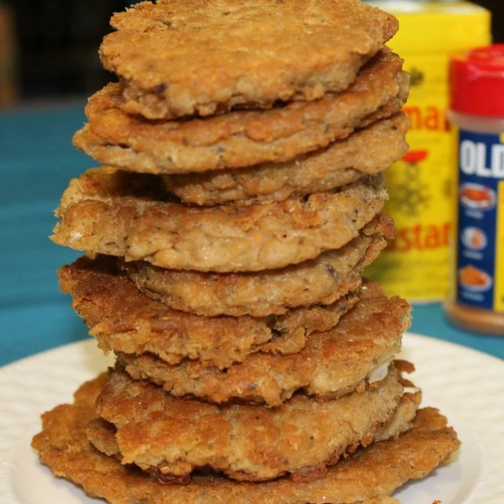 A stack of thin fried salmon patties on a plate