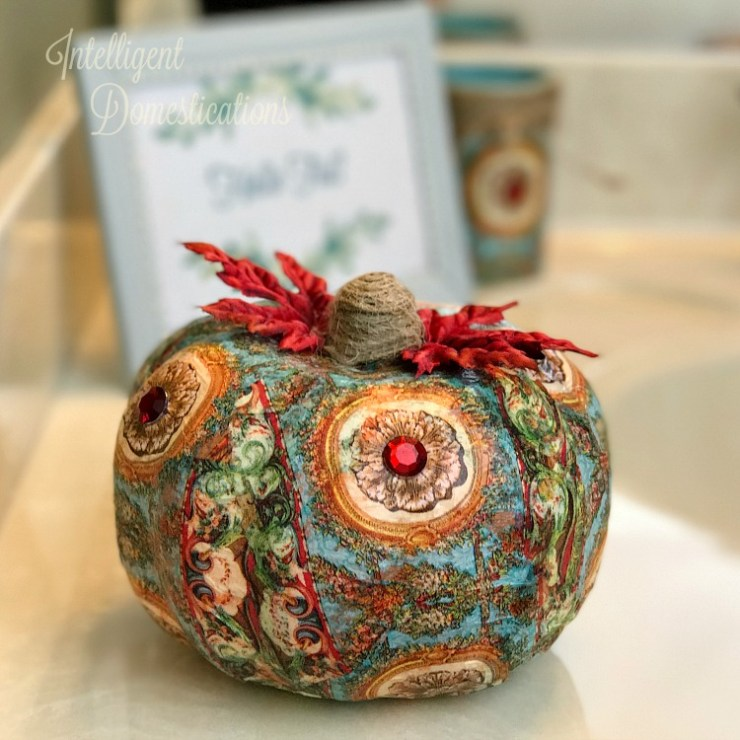 A decoupage fake pumpkin made using a pretty patterned napkin in blue, red and gold with a jute stem and fake leaves with faux jewels