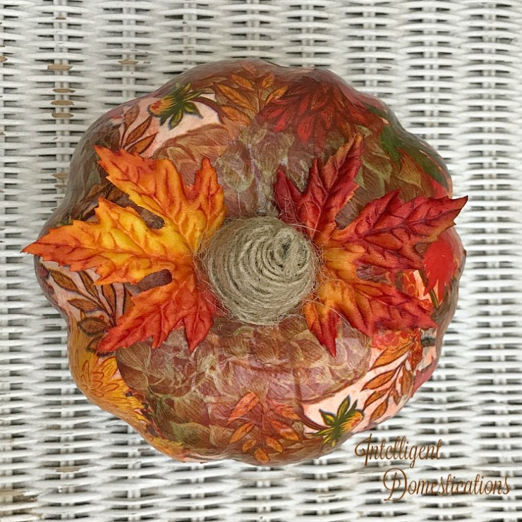A pumpkin covered in a beautiful patterned Fall napkin with orange and red faux leaves by the stem which is made of jute