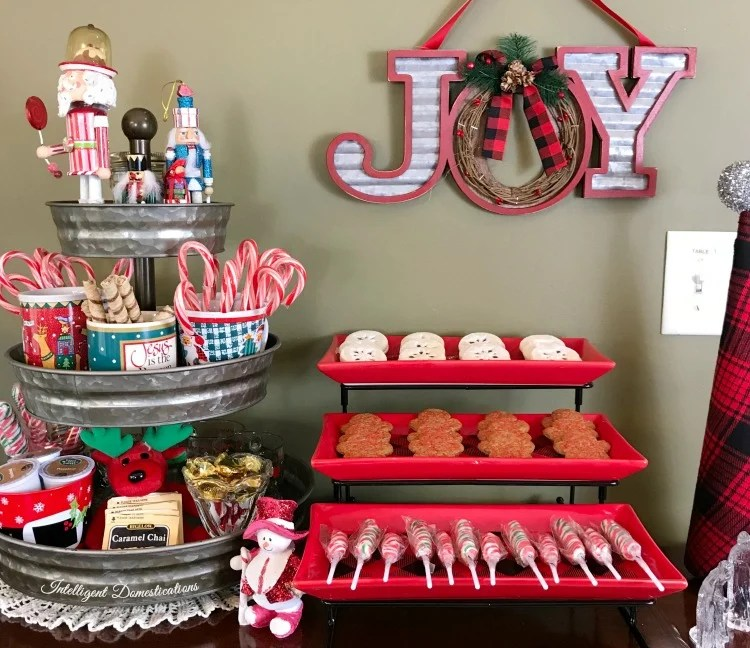 Hot cocoa bar with cookies and candies and a three tied metal tray filled with Christmas goodies