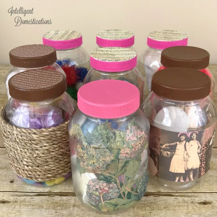 9 plastic mayonnaise jars with lids painted brown and pink and outsides decorated to be pretty craft storage containers sitting on a wood surface