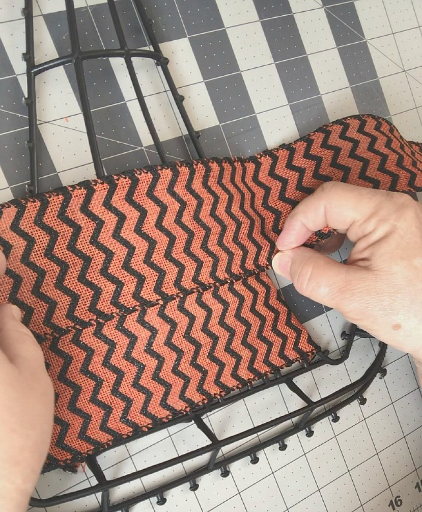 a demonstration of matching a chevron pattern while wrapping  a wreath form with ribbon
