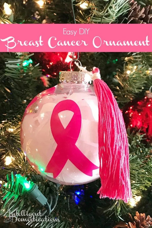 A pink and white Breast Cancer awareness Christmas ornament hanging on the Christmas tree
