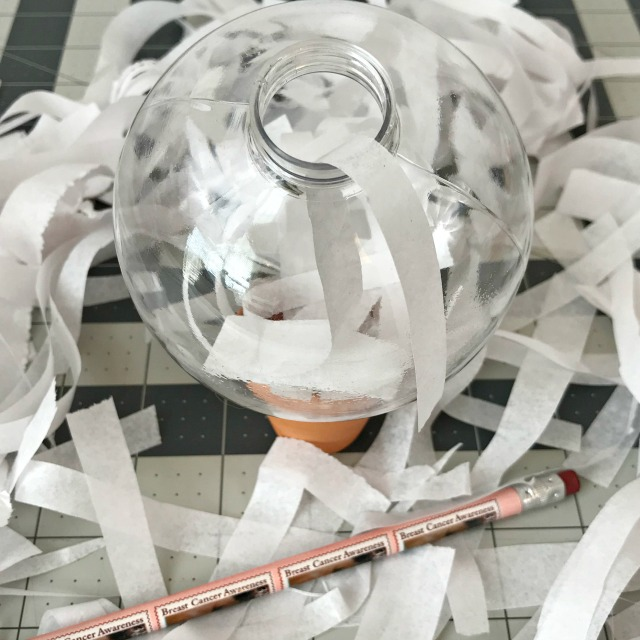 A clear Christmas ornament being filled with shredded white paper strips