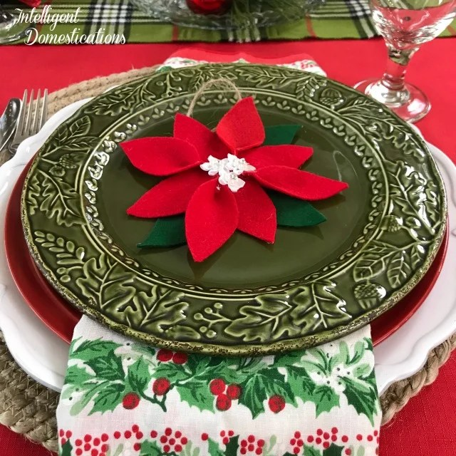 How to set a Simple Poinsettia Christmas Tablescape without using the actual flower. Bright colors and a DIY ornament decorate this festive Christmas Tablescape #Christmas #PoinsettiaTablescape #ChristmasTablescape