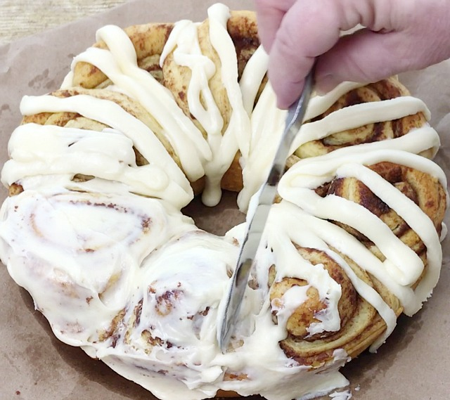 Cinnamon roll cake with icing piped on and the icing is being spread with a knife