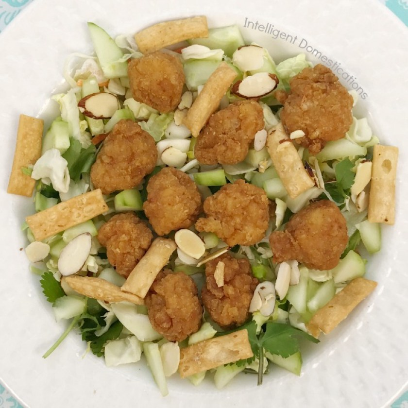 Chicken tenders piled onto an Asian Salad served in a white bowl