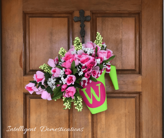 DIY Monogrammed Watering Can Wreath with bouquets of Roses spilling from the spout. I made this Spring wreath using Dollar Store supplies and my Cricut. It comes together in under one hour. Make this pretty Dollar store Spring Wreath for you home. #Wreath #diydecor