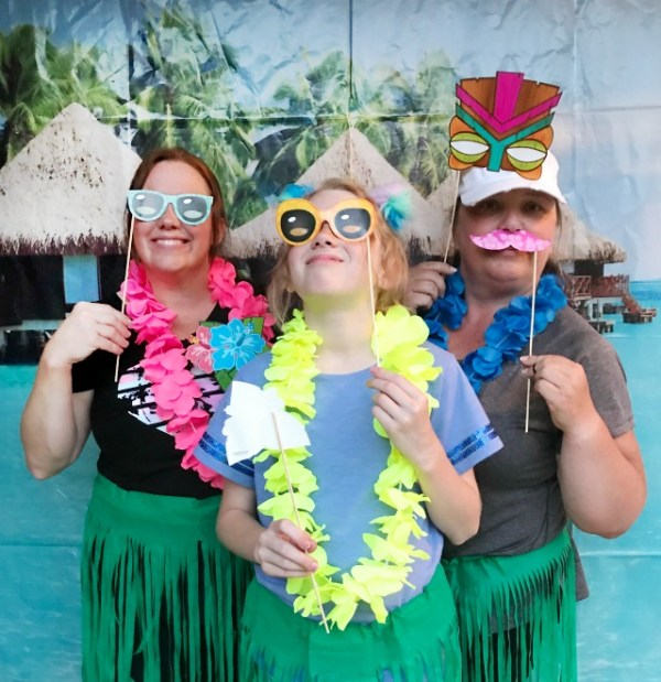 Our Backyard Luau Party was the most fun party! We set the mood with Tiki torches, Hibiscus flowers, Tropical leaves, a Tropical Cabana photo banner and a few more Tropical touches. All the details including where to buy the supplies are included. #backyardluau #luauparty #tropicalparty