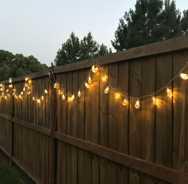 Outdoor string lights on a fence