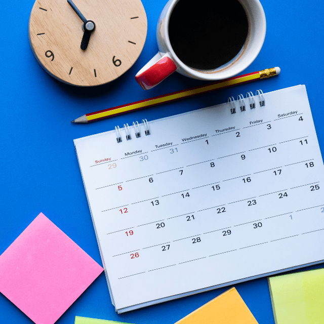 A big calendar, a clock, post it notes and a cup of coffee on a bright blue background