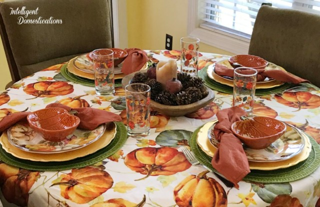 A simple Fall table setting using traditional fall colors for the dining table in the kitchen. Everyday dishes and glasses paired with a pretty Pumpkin pattern tablecloth create those cozy Fall feels. #autumn