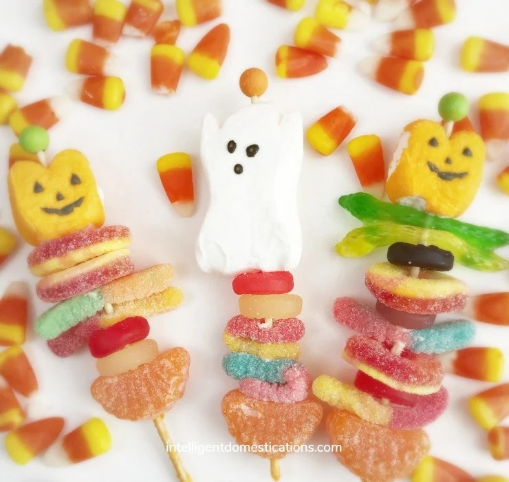 Halloween candy kabobs displayed on a white background surrounded by candy corn.