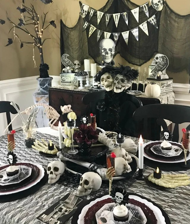 Halloween Skeleton Tablescape. This Halloween Table decor is all decked out in skulls and bones using black white and cream as the focal color scheme. If spooky Halloween is what you are after this one is spooky and creepy.
