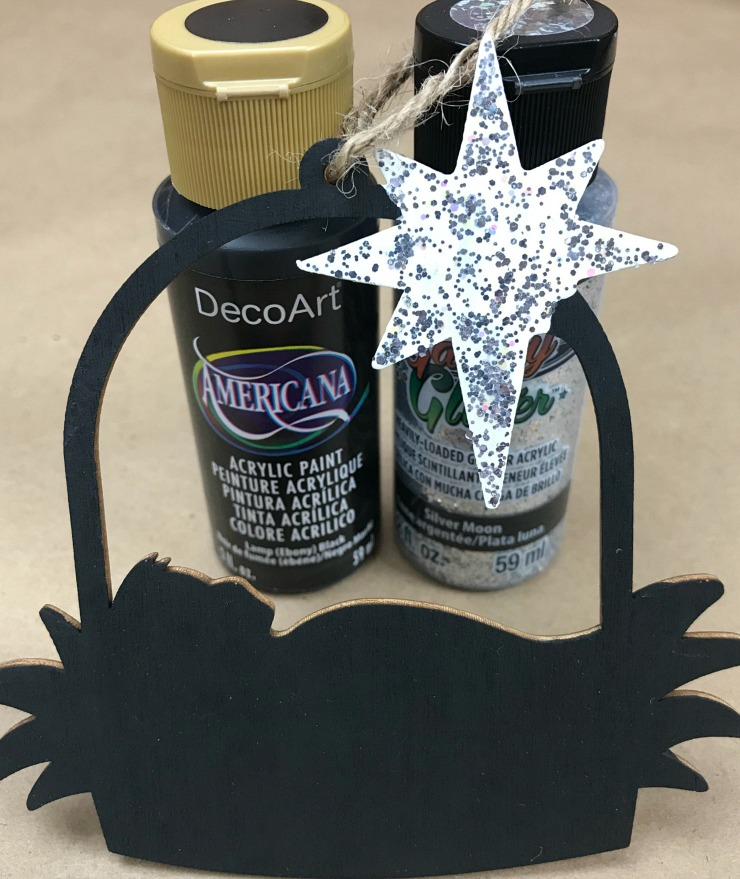 Balsam wood Nativity Christmas Ornament painted with the paint colors in the background. Black and silver