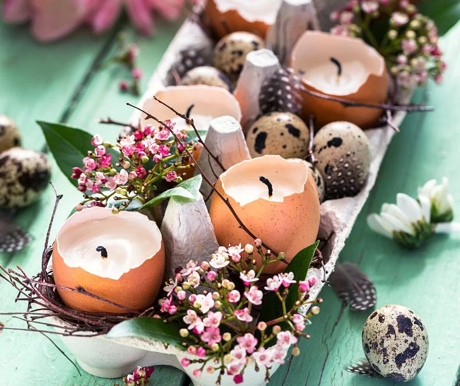 Broken egg shells made into candles sitting in a pretty decorated egg carton with tiny floral bouquets