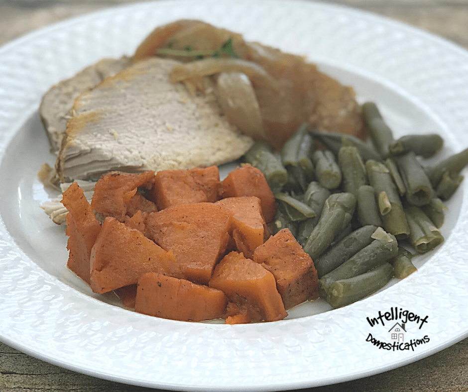 Baked pork tenderloin with green beans and candied yams served on a white dinner plate